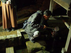 真名井の清水を汲む根本先生。防寒対策も万全です。